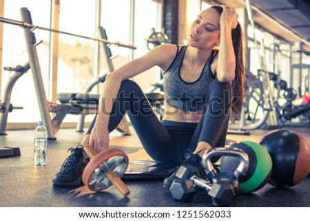 Fitness girl sitting on mat and relaxing after sports training at gym. Sensual sporty girl sitting around exercise equipment and looking away. #1251562033
