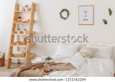 New year winter home interior decor. Christmas holiday decorations. Stylish cozy scandinavian bedroom: bed, wooden shelving, knitted blanket, plaid, wreath, pine branches, frame with text LET IT SNOW. #1251562204