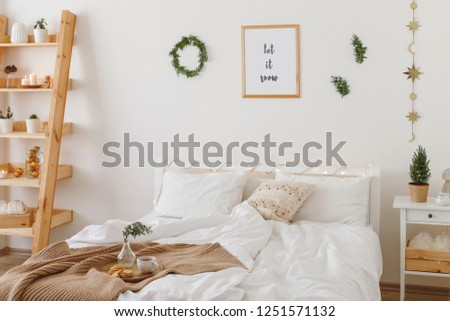 New year winter home interior decor. Holiday decorations. Stylish cozy white scandinavian bedroom: bed, knitted blanket, plaid, pillows, cushions, wreath, pine branches, little christmas tree in a pot #1251571132