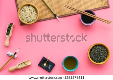 Chinese traditional symbols concept. Tea, rice, hieroglyph love, bamboo table mat, chopsticks, soy sause on pink background top view frame copy space #1251575611