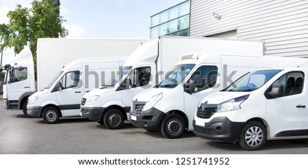 Several cars vans trucks parked in parking lot for rent or delivery #1251741952
