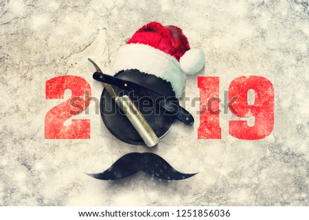 Razor on a plate for foam with a Santa Claus hat on a gray background. Inscription 2019. Greeting card Happy New Year and Merry Christmas for a hairdresser and barber shop. Snow effect