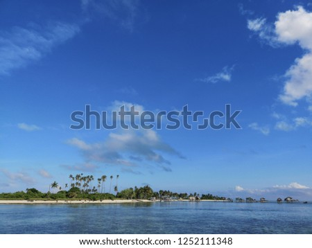 Stunning view of the ocean with coral reef, blue sky and island background. #1252111348