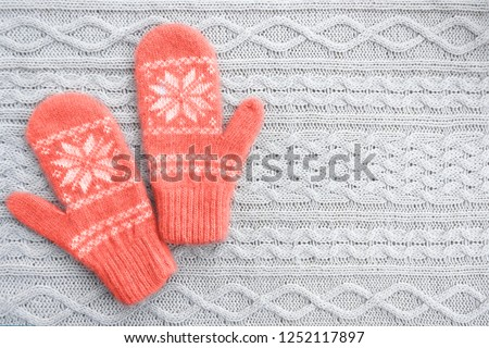 Warm woolen mittens on knitted background. Living coral creative and moody color of the picture. Color of the 2019 year.