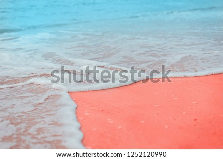 Soft blue waves of the sea with white foam on sandy beach toned Living Coral creative and moody color of the picture.