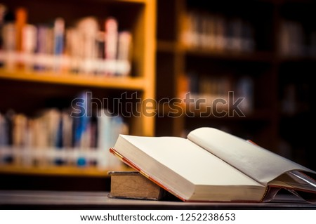 Stack of books in the library and blur bookshelf background #1252238653
