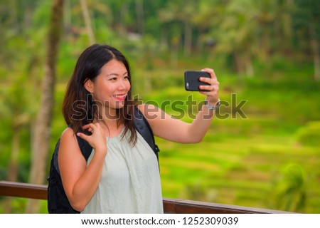 young happy and attractive Asian Korean backpacker woman taking selfie self portrait with mobile phone at tropical island posing cheerful and relaxed exploring jungle enjoying holidays travel