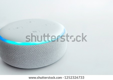 Amazon echo dot, voice controlled speaker with activated voice recognition, on light background. #1252326733