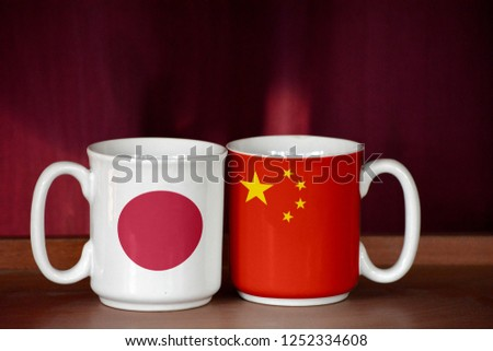 China and Japan flag on two cups with blurry background #1252334608