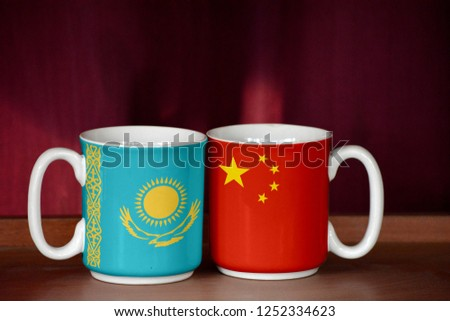 China and Kazakhstan flag on two cups with blurry background #1252334623