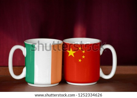 China and Ireland Ireland flag on two cups with blurry background #1252334626
