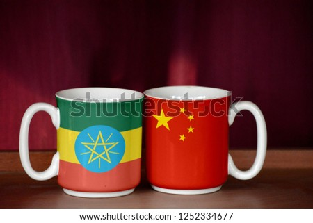 China and Ethiopia flag on two cups with blurry background #1252334677
