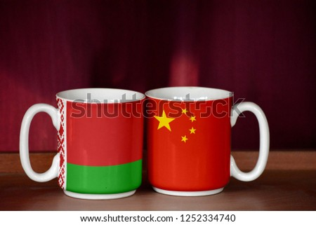 China and Belarus flag on two cups with blurry background #1252334740