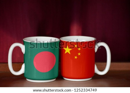 China and Bangladesh flag on two cups with blurry background #1252334749
