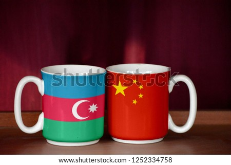 China and Azerbaijan flag on two cups with blurry background #1252334758