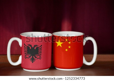 China and Albania flag on two cups with blurry background #1252334773