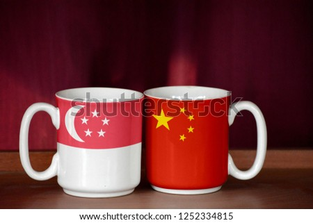 China and Singapore flag on two cups with blurry background #1252334815