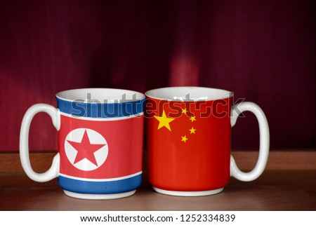 China and North Korea flag on two cups with blurry background #1252334839