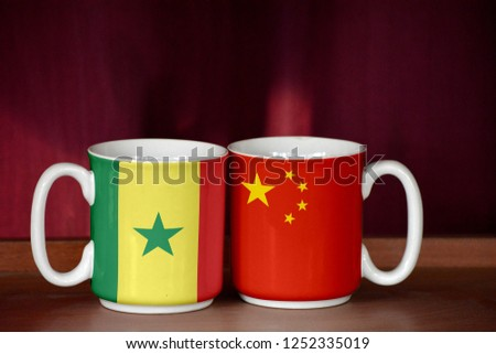China and Senegal flag on two cups with blurry background #1252335019
