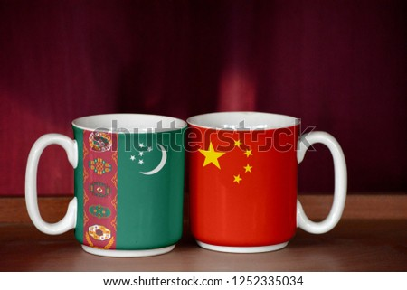 China and Turkmenistan flag on two cups with blurry background #1252335034