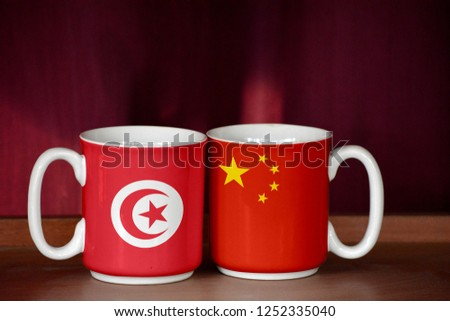 China and Tunisia flag on two cups with blurry background #1252335040