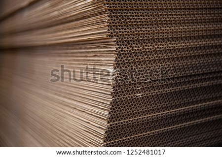 Corrugated cardboard sheets are one by one, they are prepared for the production of cardboard boxes. Polygraphic background of cardboard #1252481017