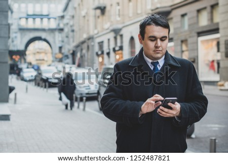 View of  plump guy using smartphone, Young urban businessman professional on smartphone walking in street using app texting sms message on smartphone