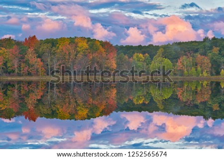 Autumn landscape at dawn of the shoreline of Deep Lake with mirrored reflections in calm water, Yankee Springs State Park, Michigan, USA Royalty-Free Stock Photo #1252565674