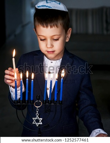 A vertical image of a sweet Caucasian Jewish boy lighting candles on the Jewish holiday Chanukah.
