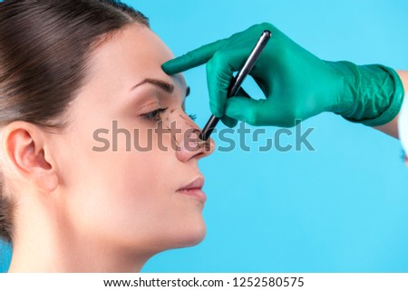 Cosmetic surgeon examining female client in office. Doctor draws lines with a marker, the eyelid before plastic surgery, blepharoplasty. Surgeon or beautician hands touching woman face. Rhinoplasty #1252580575