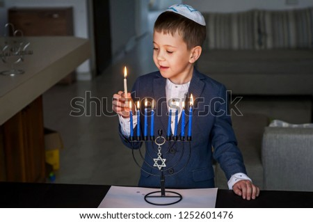 Cute Caucasian Jewish boy lighting candles on a traditional Hanukkah menorah candelabrum, Jewish holiday Chanukah concept.