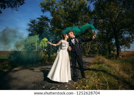 Wedding couple hold color smoke in their hands in the middle of alley #1252628704