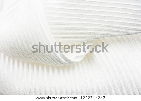 The texture is ribbed, patchy, pleated fabric on the background screen, close-up. Pearl Color #1252714267