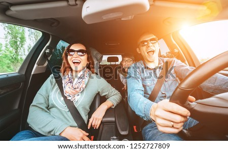 Cheerful young traditional family has a long auto journey and singing aloud the favorite song together.  Safety riding car concept wide angle view image. #1252727809