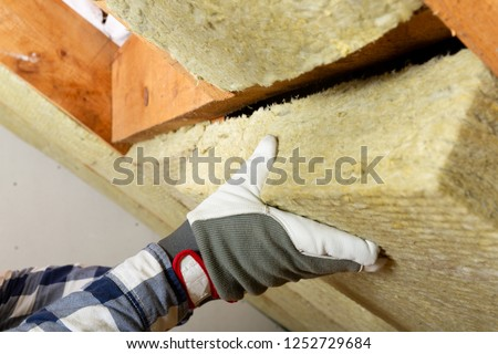 Man installing thermal roof insulation layer - using mineral wool panels. Attic renovation and insulation concept #1252729684