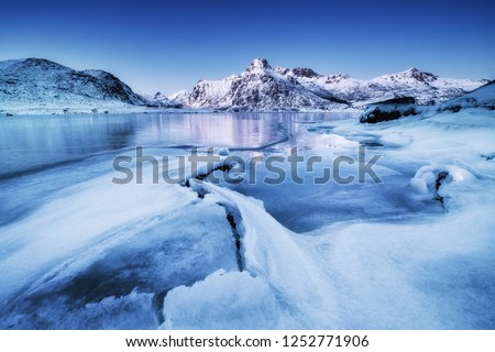 Mountain ridge and ice on the frozen lake surface. Natural landscape on the Lofoten islands, Norway. Water and mountains during sunset. Royalty-Free Stock Photo #1252771906