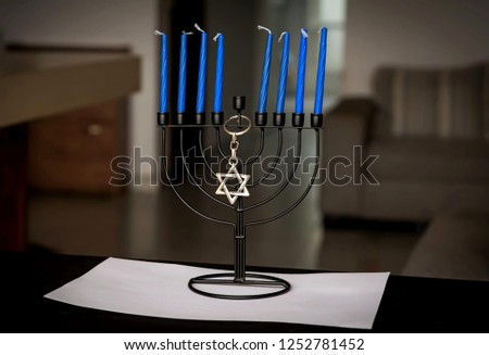 Traditional Jewish Chanukah Menorah candelabrum with eight blue candles and a Star of David key chain on a table, Jewish holiday Hanukah concept image.