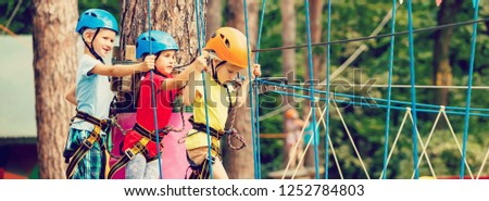 Child in forest adventure park. Kids climb on high rope trail. Agility and climbing outdoor amusement center for children. Little girl playing outdoors. School yard playground with rope way. #1252784803