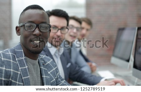 young businessman and his business team sitting at the Desk #1252789519