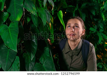 girl traveler in the jungle at dusk frightened looks up at something #1252796599