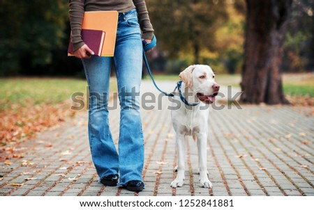 Young woman holding books in a hand while walking with a dog. Friendship between human and dog. Pets and animals concept #1252841881