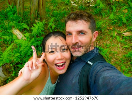 young beautiful and happy mixed ethnicity couple beautiful Asian Chinese woman and white man in love taking selfie picture outdoors enjoying romantic holidays trip in tropical honeymoon vacation