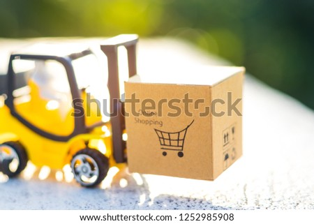Mini forklift truck load cardboard box with shopping cart symbol with natural green background on sunny day. Logistics and transportation management ideas and Industry business commercial concept. #1252985908