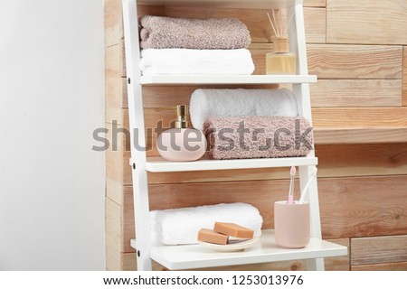 Towels, toiletries and soap dispenser on shelves in bathroom #1253013976