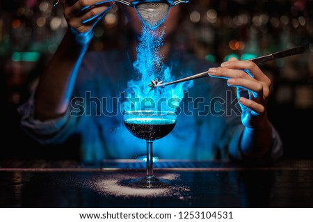 Bartender girl adding to a brown cocktail and pour on a flamed badian on tweezers a powdered sugar on the bar counter in the blue light. #1253104531