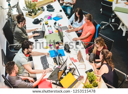 Young co-workers team talking during startup - Happy people planning a new project in creative workplace office - Technology, entrepreneur, marketing and concept - Focus on left man with headphones Royalty-Free Stock Photo #1253115478
