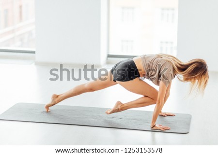 young ambitious sportswoman doing exercises in the health studio. full length side view shot #1253153578