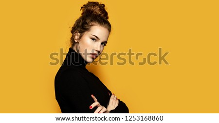Portrait of beautiful girl posing for fashion photoshoot on yellow background. Pretty model dressed in stylish black pullover. Trend and lifestyle concept #1253168860