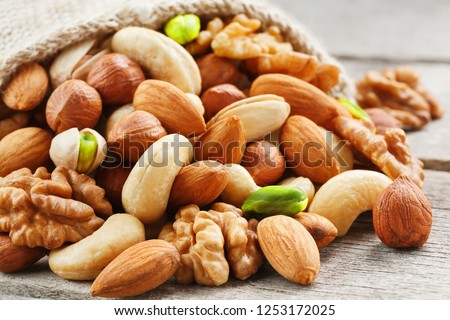 Mix of different nuts in a wooden cup against the background of fabric from burlap. Nuts as structure and background, macro. Top view. Royalty-Free Stock Photo #1253172025