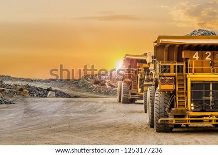 Large Yellow Dump Trucks transporting Platinum ore for processing #1253177236